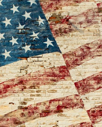 Old Glory fading on brick wall